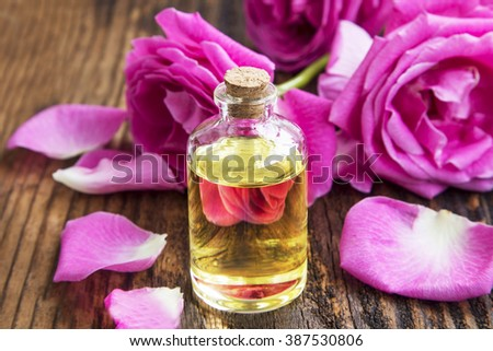 Rose essential oil in a bottle with pink roses and petals on wooden board