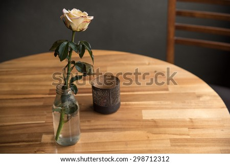rose in a bottle on a coffee table near the brick wall - stock photo