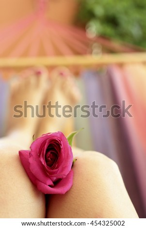 Rose on the knees of a woman who is lying in a hammock