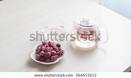 rose petals and dried flowers in spoon on old table - stock photo