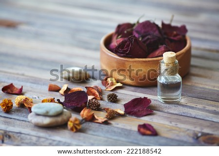 Rose petals and vial with rose essence - stock photo