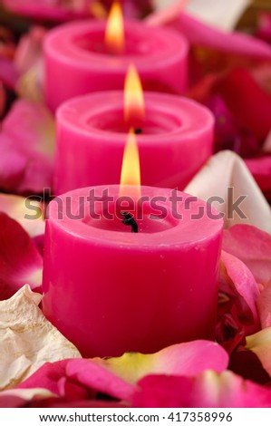 Rose Petals background with red three candle - stock photo
