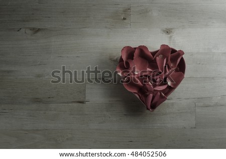 Rose petals filling a heart shaped bowl, in old, faded dark plum hues.  Shot overhead on a wood planked surface.  Faded with low saturation for a moody retro or vintage effect.