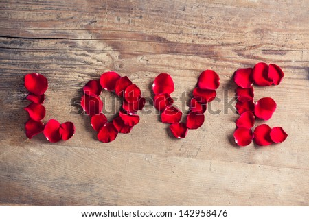 Rose petals forming the word love.