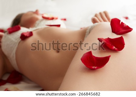 Rose petals on hip of sexy lingerie model, close-up - stock photo