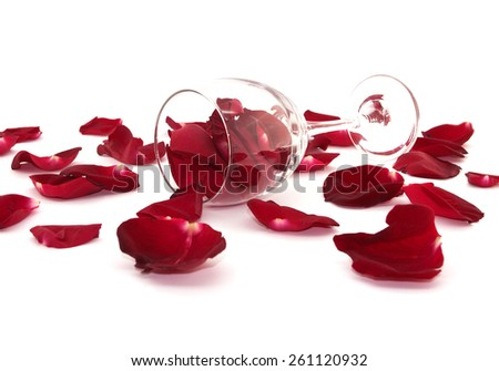 Rose petals, wine glass isolated on a white background. Love concept, selective focus.