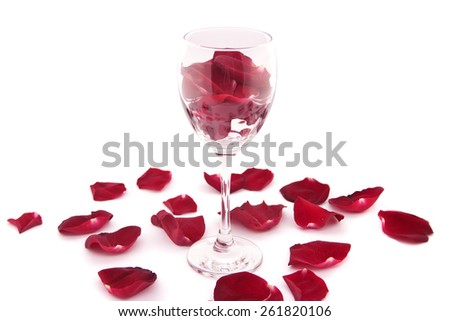 Rose petals, wine glass isolated on a white background. Love concept, selective focus. - stock photo