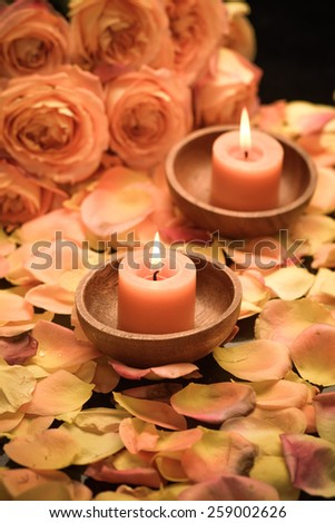 rose petals with rose with two candle in wooden bowl  - stock photo