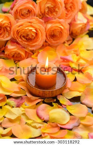 Rose with many rose petals with candle in wooden bowl  - stock photo