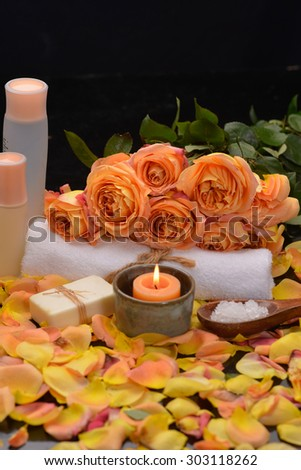 rose with petals with candle in bowl, towel -black background  - stock photo