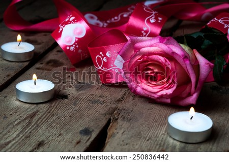 Rose wrapped in satin ribbon and candles.Romantic setting. - stock photo