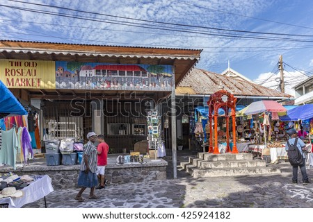 ROSEAU, DOMINICA - APR 27, 2016: people visit the old Roseau market with the historic red statue in the middle. The market was once a slave market. - stock photo