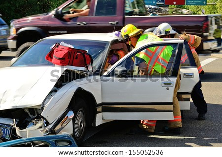 ROSEBURG, OR - AUGUST 27, 2013: Firefighters and paramedic emt personnel extricate the victim of a two vehicle head on accident at an intersection in Roseburg, OR on August 27, 2013 - stock photo