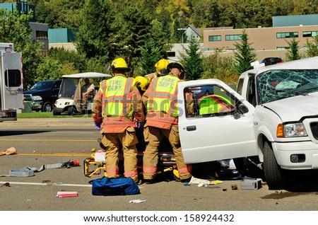 ROSEBURG, OR - SEPTEMBER 11, 2013: Firefighters extricate victims of a two vehicle t-bone accident at an intersection resulted in major injuries in Roseburg, Oregon on September 11, 2013 - stock photo