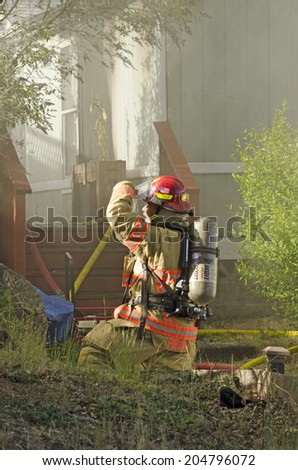 ROSEBURG, OR, USA - JUNE 10, 2014:  Firefighters respond to a single family home fire on a hot summer day in Roseburg, OR, USA on June 10, 2014