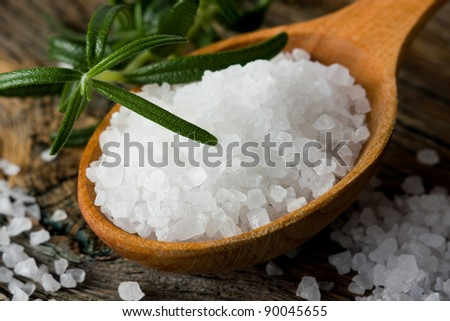 Rosemary and healthy sea salt on wooden spoon closeup - stock photo