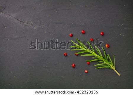 Rosemary and red pepper seeds on gray stone plate.