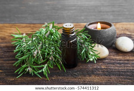 Rosemary aromatherapy oil with rosemary herb on wooden background with candle