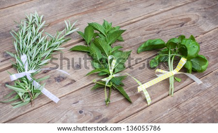 Rosemary, basil and peppermint plants in bunch on wooden table in summer