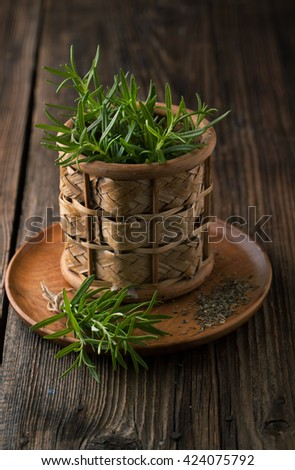 Rosemary fresh bound in a basket and wooden board on a wooden background