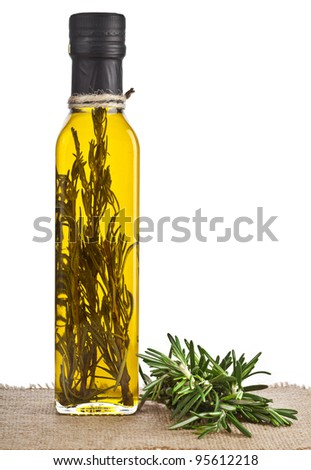 Rosemary oil bottle with fresh twig herb rosemary in sacking, isolated on white background - stock photo
