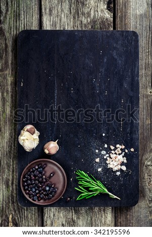 Rosemary, salt and pepper on wooden cutting board, copy space. Cooking food background - stock photo