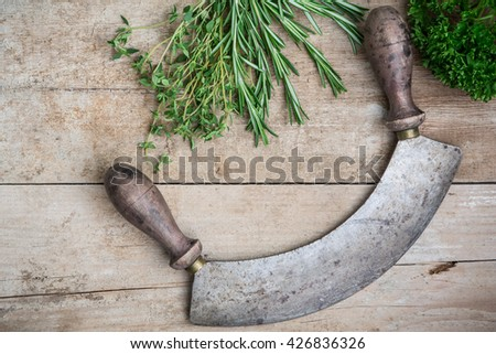 Rosemary, thyme and parsley with a rusty chopping knife on an old wooden board
