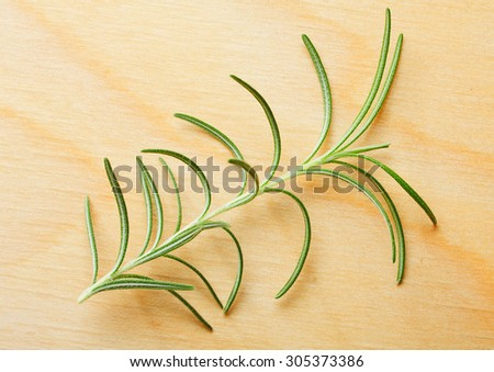 Rosemary twig over wood board background
