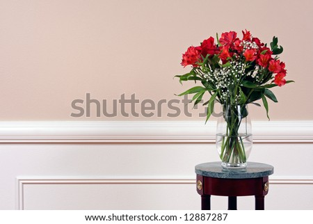 Roses and Alstroemeria in a crystal vase on a marble stand. - stock photo