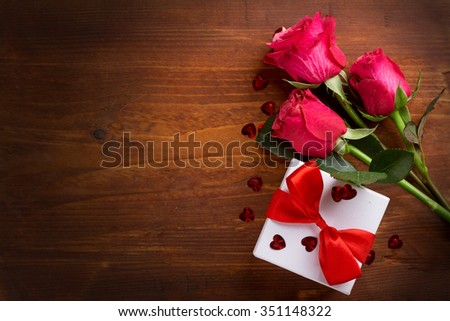 Roses and gift on wooden board, Valentines Day background, selective focus
