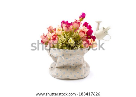 Roses and small watering pot in fabric vase on white - stock photo