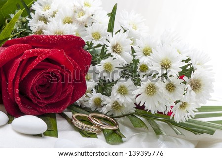 roses and wedding rings on white background - stock photo