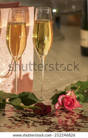 Roses, champagne, petal and heart shaped confeti, some effects used to remove certain colours from image and median noise reduction also used on some images to produce a faded look, - stock photo