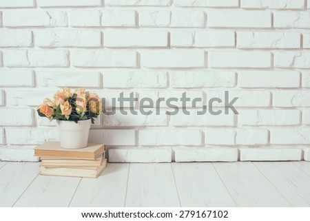 Roses in a vase and a stack of old vintage books on a  white brick wall background, room interior. - stock photo