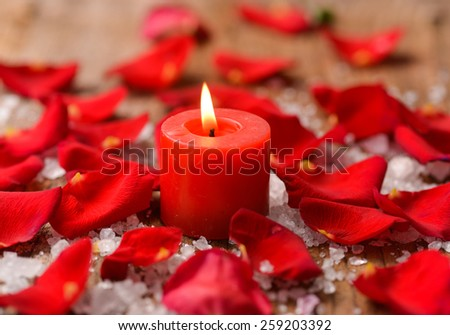 Roses petals with pile of salt ,stones on old wooden board
