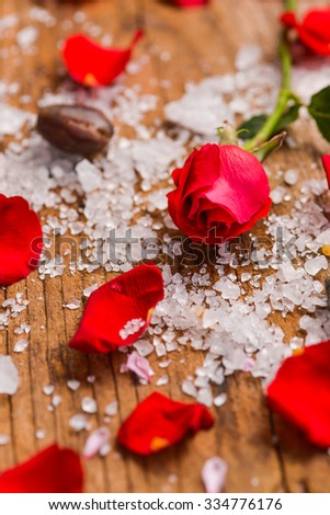 Roses with pile of salt on old wooden board