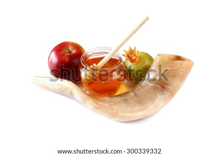 rosh hashanah (jewesh holiday) concept - shofar (horn), honey, apple and pomegranate isolated on white. traditional holiday symbols.