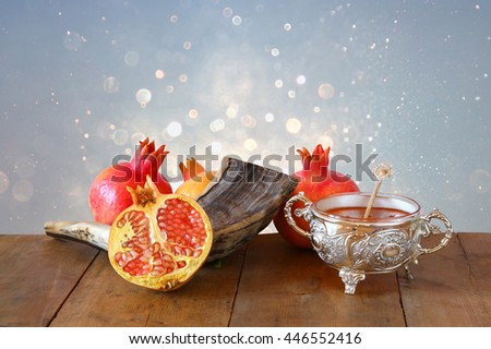 Rosh hashanah (jewish New Year holiday) concept - honey, shofar (horn) and pomegranate over wooden table. Traditional symbols - stock photo