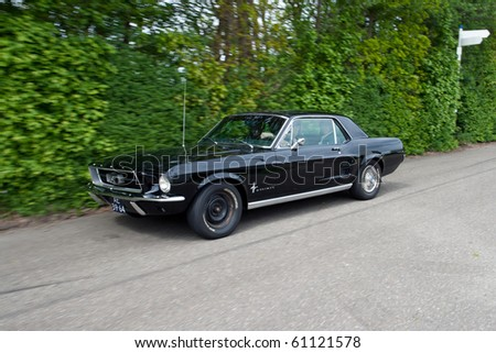 ROSMALEN, THE NETHERLANDS - MAY 16: Black 1967 Ford Mustang HTP Coupe arriving on the Rock Around the Jukebox Open Air event on May 16, 2010 in Autotron Rosmalen in Holland. - stock photo