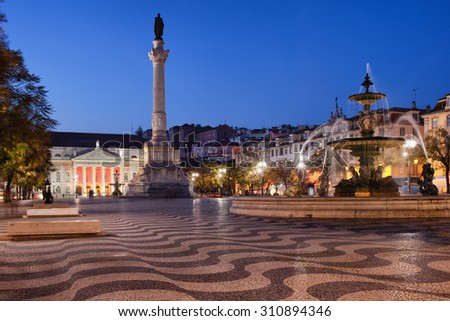 Rossio Square at night in Lisbon, Portugal with Column of Dom Pedro IV, Baroque fountain and Dona Maria II National Theater.