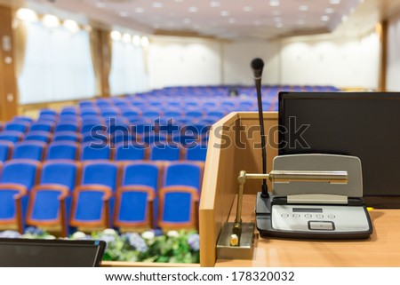 Rostrum with microphone and computer in conference hall - stock photo