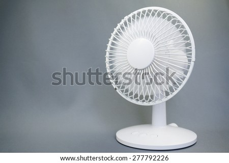 Rotating electric fan on gray background - stock photo