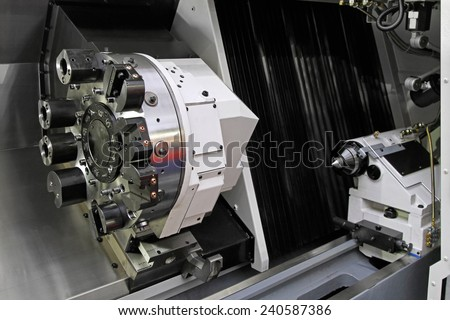 Rotating head at CNC lathe in workshop - stock photo