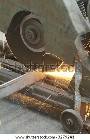 Rotating, industrial steel cutter in an industrial workshop with sparks flying.