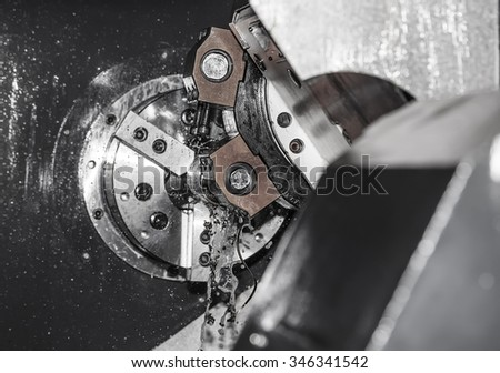 Rotating shiny metal part of the CNC lathe - stock photo