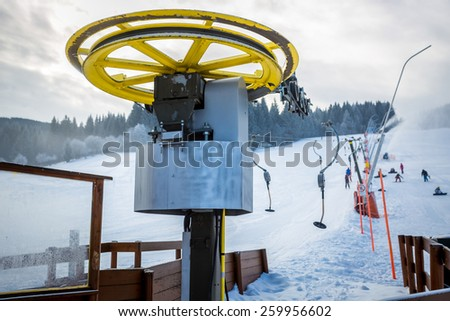 Rotating ski lifts mechanism on foot of high mountain at Alps - stock photo