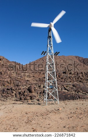 rotating small wind generator on a mast in a desert with the rocky mountains and a blue sky  - stock photo