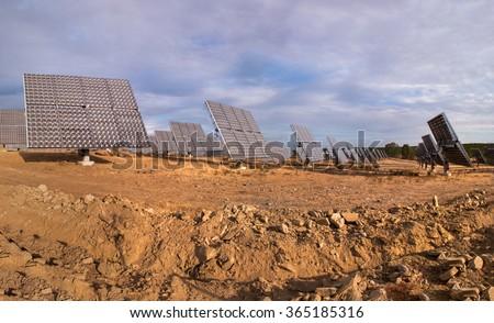 Rotative photovoltaic solar panels park on dry land. - stock photo