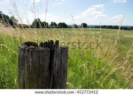 Rotten post in the corner of a field in England. - stock photo