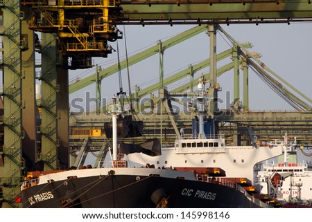 ROTTERDAM - JULY 9: Bulkcarriers unloading cargo on July 9, 2013 in Rotterdam, the Netherlands. Rotterdam is the main European harbour and was the world's largest container port from 1962 until 2002 - stock photo
